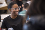 student in a black top and acrylic glasses smiling in a wharton classroom