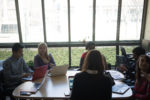 a group of students working on laptops and discussing projects in the WSII office