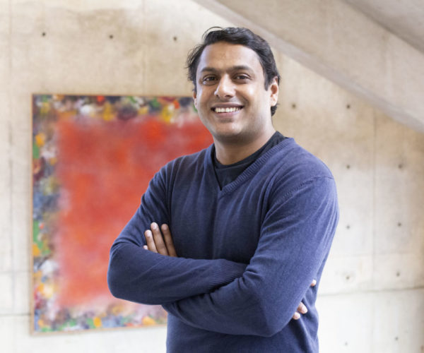 Raj Sebastian headshot with painting in background. He wears a blue shirt.