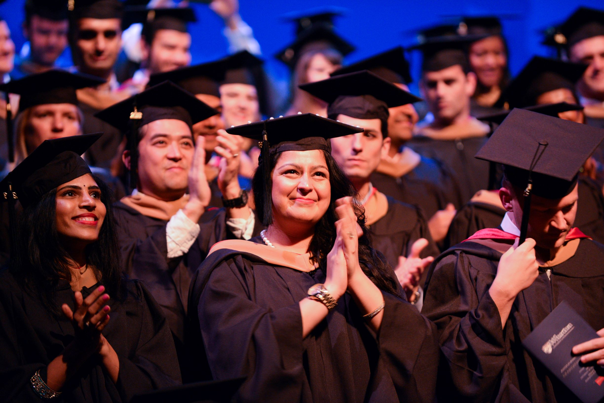 large group of MBA graduates at a commencement ceremony, clapping and smiling