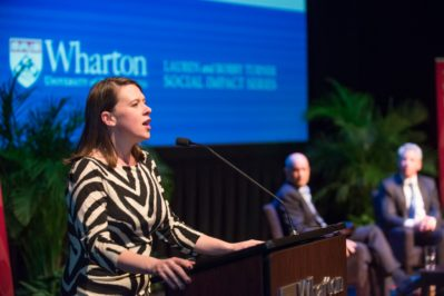 Sandi Hunt speaking at a podium in front of a blue screen showing Wharton's logo