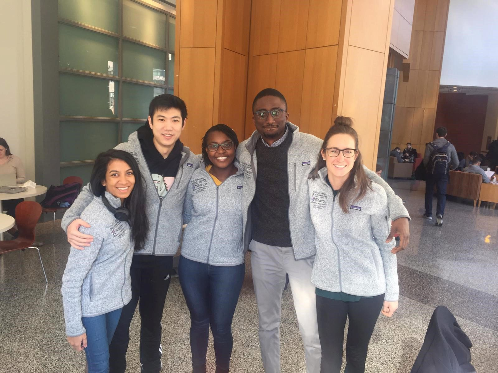 five WAG students, arms around each other, wearing matching WAG gray fleece