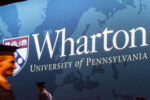 closeup of a graduate in cap and gown walking in front of a sign with the Wharton School logo